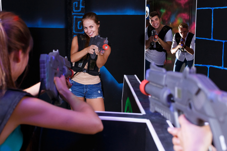 Excited young positive people playing enthusiastically laser tag game two teams opposite each other in dark room