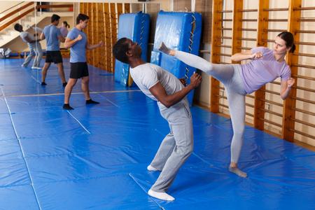 Junges Mädchen und afroamerikanischer Mann üben Selbstverteidigungstechniken im Fitnessstudio Standard-Bild