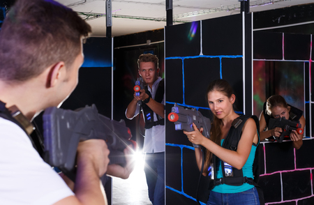 Emotional young people enthusiastically playing laser tag in dark room (first-person view) Stock Photo