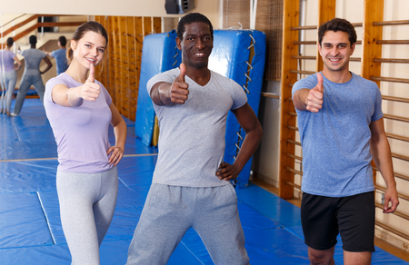 Portrait of satisfied young fit men and woman posing after workout at gym Foto de archivo