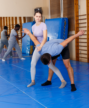 Adult people practicing effective techniques of self-defence in training room Stockfoto