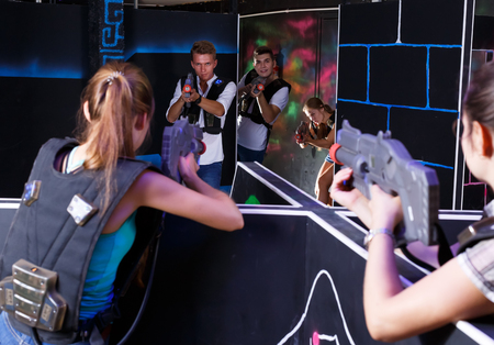 Two teams of laser tag game girls and guys playing  opposite each other in dark room