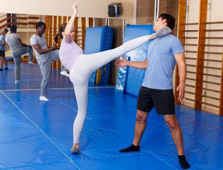 Frau und Mann üben Selbstverteidigungstechniken im Fitnessstudio practicing