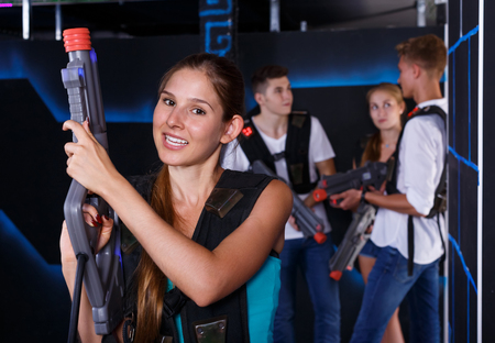 Positive girl holding laser pistol during playing lasertag game with her friends in dark room
