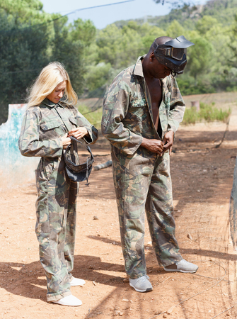 adult male and female paintball players getting ready for match outdoors, dressing camouflages