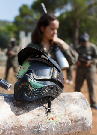 Closeup of black paintball mask with splash after direct hit from marker gun after match outdoors