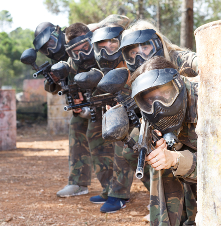 Portrait of team of adult people playing on paintball battlefield outdoor Фото со стока