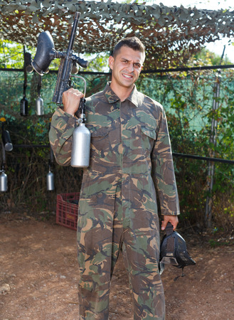Portrait of male paintball player with marker gun ready for game outdoors