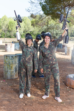Portrait of two female paintball players with marker guns ready for game outdoors