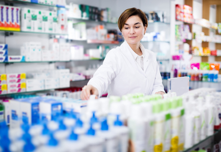 Young woman pharmacist organizing assortment of care products in pharmacy