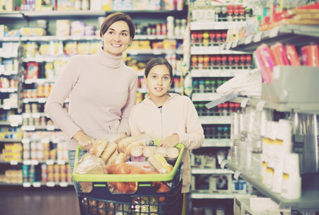 Smiling female customer with teenage daughter restocking for family in supermarket