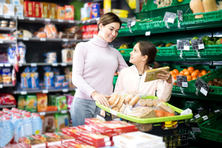 Beautiful young female shopper with teenage daughter searching for cookies in supermarket