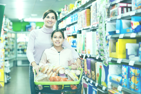 Young woman customer with girl looking for food supplies in a supermarket. Focus on child Фото со стока
