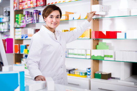 Smiling girl is searching for body care products in drugstore.