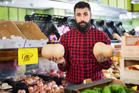 Young cheerful positive male seller offering pumpkins in grocery shop