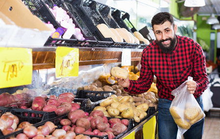 Young glad  positive male seller offering potatoes in grocery shop Фото со стока