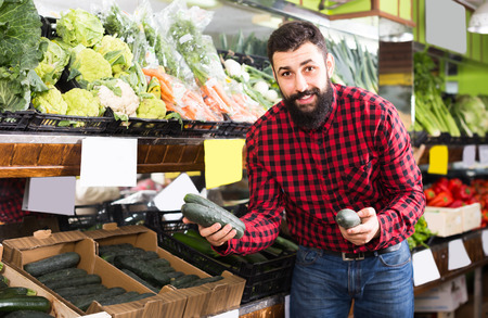 Cheerful male seller offering cucumbers in grocery shop