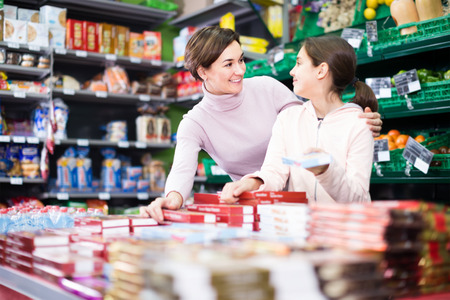 glad woman with daughter choosing delicious cookies in supermarket