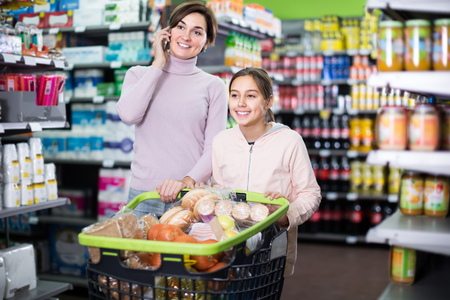 woman consulting on phone while shopping with daughter in supermarket