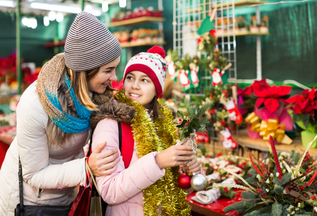 positive russian woman with daughter looking at floral decoration at Cristmas fair