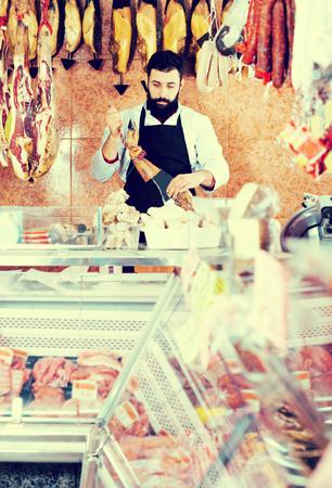 Glad male shop assistant demonstrating jamon in butcher's shop