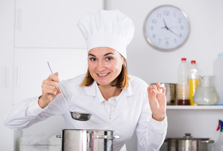 Young female cook tasting food while preparing in kitchen Imagens - 124797809