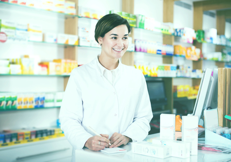 Glad young woman pharmacist ready to assist in choosing at counter in pharmacy Фото со стока