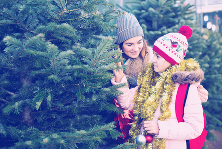 cheerful girl with mom choosing New Years tree outdoors Stock Photo