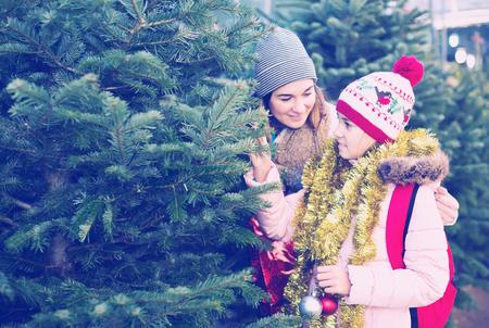 cheerful girl with mom choosing New Years tree outdoors Фото со стока