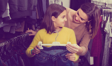 Mother and cheerful teenager choosing trendy jeans in children's cloths store