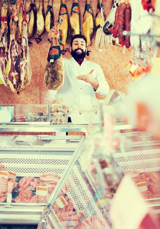 Positive man seller showing jamon in butcher's shop