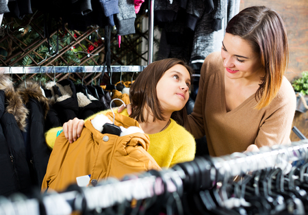 Young mother and daughter examining various coats in children's cloths shop Фото со стока