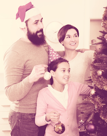 Portrait of young glad family decorating Christmas tree at home 스톡 콘텐츠