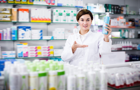 Young female pharmacist offering products of body care in pharmacy Фото со стока