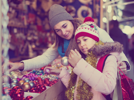 joyous mother with little daughter buying decorations for Xmas at an open air market