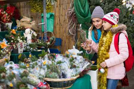 Happy mom and girl buying  flowers decoration at Christmas market