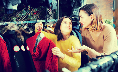 Woman and girl buying warm sweater in children's cloths store