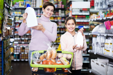 Glad female client with teenage daughter restocking for family in supermarket. Focus on girl
