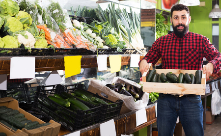 Glad young male shop assistant demonstrating zucchinis in grocery shop