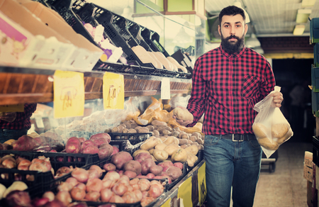 Young  cheerful positive male seller offering potatoes in grocery shop