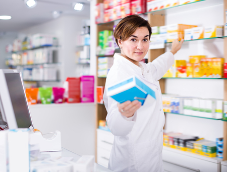 Beautiful pharmacist offering reliable medicine in pharmacy
