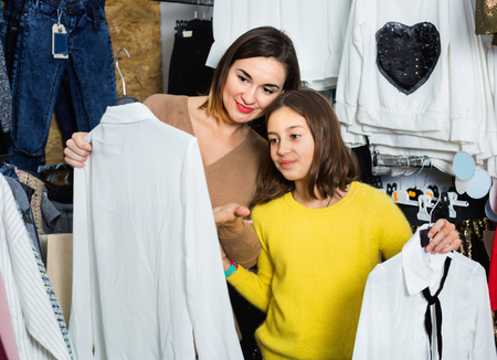 Mother and happy cheerful daughter choosing pretty blouse in children's cloths shop