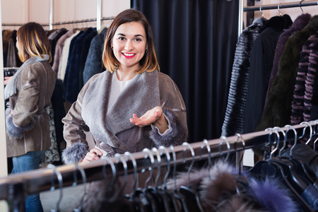 Cheerful positive woman trying on sheepskin coat in women's cloths store