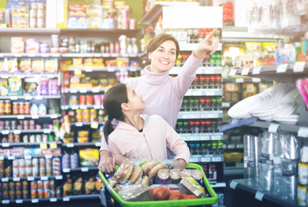 Smiling female client with teenage daughter restocking for family in supermarket Фото со стока