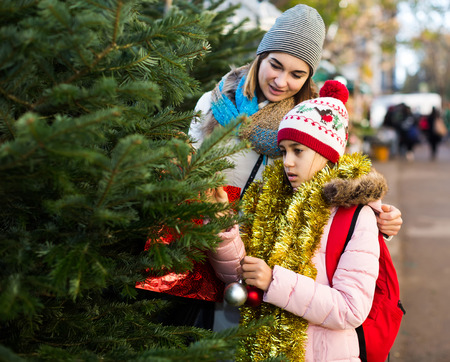 american  mother and daughter staying at market among Christmas trees. Focus on girl