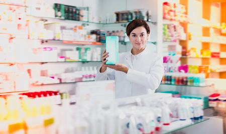 Adult female pharmacist offering products of body care in pharmacy