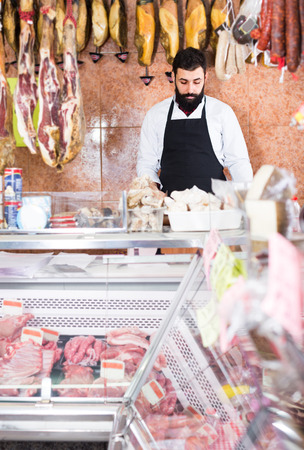 young shop assistant arranging meat to sell in butcher's shop Фото со стока