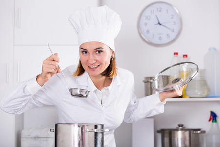 Young female cook tasting food while preparing in kitchen Imagens - 124799708