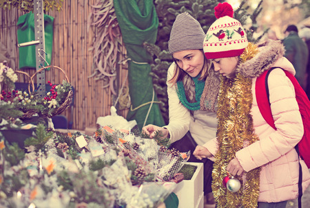 Young mom and girl looking at flowers decoration at Christmas market Banco de Imagens
