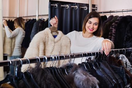 Happy positive woman choosing white mink jacket in women's cloths store